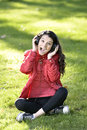 Woman listening to music female student girl outside in park on headphones while studying happy young Stock Image