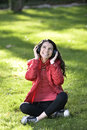 Woman listening to music female student girl outside in park on headphones while studying happy young Royalty Free Stock Photo