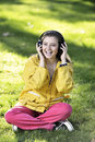 Woman listening to music female student girl outside in park on headphones while studying happy young Stock Photography