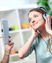 Woman listening to music while her husband takes pictures pretty women with headphones with a tablet Royalty Free Stock Photo