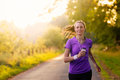 Woman listening to music while jogging on her earplugs and mp player along a country road in a healthy lifestyle exercise and Royalty Free Stock Image