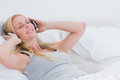 Woman listening to music while she is laid in her bed blonde Royalty Free Stock Photos
