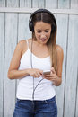 Woman listening wireless music with headphones from a smart phone Royalty Free Stock Photo