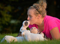 Woman and litter of puppies playing in the grass with Stock Photo