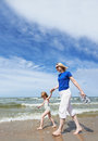 Woman and little child walking at sea beach Stock Photography