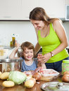 Woman with little girl cooking together smiling women at home kitchen Royalty Free Stock Image