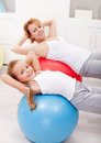Woman and little girl exercising with large balls at home Royalty Free Stock Photos