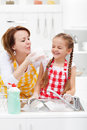 Woman and little girl having fun washing the dishes playing with foam Royalty Free Stock Images
