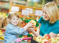Woman and little girl shopping fruits choosing apple during at fruit vegetable supermarket Stock Images
