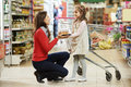 Woman and little girl shopping fruits choosing apple during at fruit vegetable supermarket Stock Photos