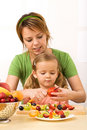 Woman and little girl slicing fruits Royalty Free Stock Photo
