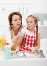 Woman and little girl washing dishes having fun with the foam in kitchen Royalty Free Stock Photography