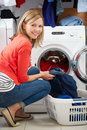 Woman loading clothes into washing machine smiling at camera Stock Photography