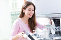 Woman loading dishwasher and smiling Royalty Free Stock Photos