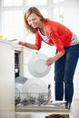 Woman loading plates into dishwasher in kitchen smiling Royalty Free Stock Image