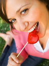 Woman with a lollipop heart shaped outdoors love is written on the Royalty Free Stock Image