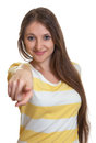 Woman with long brown hair pointing at camera attractive on an isolated white background Royalty Free Stock Images