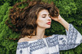 Woman with long curly hair lying on spring grass Royalty Free Stock Photo