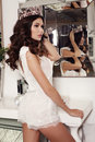 Woman with long dark hair wears elegant lace suit and precious crown Royalty Free Stock Photo