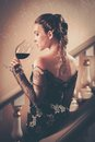 Woman in long evening dress beautiful young with glass of red wine standing on a steps luxury interior Royalty Free Stock Photos