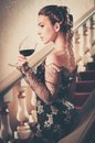 Woman in long evening dress beautiful young with glass of red wine standing on a steps luxury interior Royalty Free Stock Photo