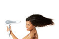 Woman with long hair holding blow dryer strong Royalty Free Stock Images