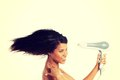 Woman with long hair holding blow dryer Royalty Free Stock Photo