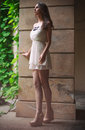 Woman with long legs walking outdoors in white dress Royalty Free Stock Photo