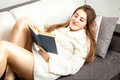 Woman in long sweater lying on couch and reading beautiful sexy book Royalty Free Stock Photo