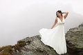 Woman in long white dress on mountain top beautiful bride standing the edge of surrounded by fog Stock Photography