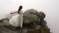 Woman in long white dress near abyss mystery bride standing on the edge of windy mountain top surrounded by fog Royalty Free Stock Images