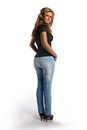 Woman looking behind her a young pretty in jeans and black blouse standing from the back in the studio blond girl with a big butt Stock Photo