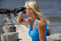 Woman looking through binoculars adult and smiling wale watching bird watching or people watching Royalty Free Stock Photography