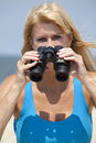 Woman looking through binoculars adult and smiling wale watching bird watching or people watching Royalty Free Stock Photo