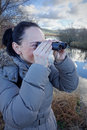 Woman looking through binoculars birdwatching on wetland Royalty Free Stock Images