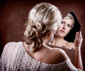 Woman looking into a broken mirror with back of head showing Stock Photos