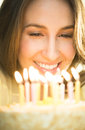 Woman looking at cake with lit candles closeup of happy young Stock Photo