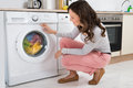 Woman looking at clothes rotating inside the washing machine young in kitchen home Royalty Free Stock Photography