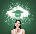 Woman looking at the cloud with graduation hat over the head. Green chalk board as a background. Royalty Free Stock Photo