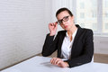 Woman looking disdainfully lifting eye glasses in suit Royalty Free Stock Photography