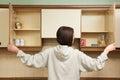 Woman looking in empty food cupboards looks Stock Image