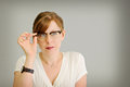 Woman looking through eye glasses holding wearing white Royalty Free Stock Photo