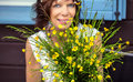 Woman looking happy behind flowers smiling has a nice time a bunch of self picked buttercups Stock Photos
