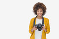 Woman looking at her digital camera and smiling on white background Stock Image