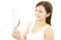 Woman looking her face in a mirror beautiful herself on Royalty Free Stock Photo