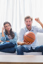 Woman looking at her husband cheering the basketball game home on couch Royalty Free Stock Images