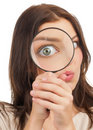 Woman looking through a magnifying glass Royalty Free Stock Photography