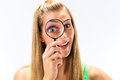 Woman looking through magnifying glass Stock Photo