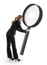 Woman looking through a magnifying glass giant Stock Photography