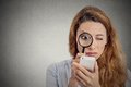 Woman looking through magnifying glass on smart phone screen Royalty Free Stock Photo